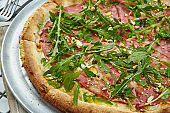 Tasty pizza with salami, arugula and parmesan on a white background. Italian traditional cuisine. Delicious food flat lay. Top view