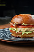 Appetizing and juicy cheeseburger with, chicken burger, tomato, caramelized onions and melted cheese in a black ceramic plate on a copper, metal background. Close up. Street food