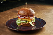 Appetizing and juicy burger with beef, tomato, onion, lettuce, bacon and melted cheese in a dark ceramic plate on a copper, metal background