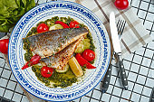 Close up view on fresh pan-fried seabass served with potato and tomato cherry in white plate. Food photo for menu or recipe. Selective focus. Healthy seafood for lunch sea bass