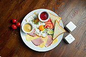 Classic English breakfast: toasts, smoked sausages, fried eggs, potato and fried toasts on a white plate on wooden background