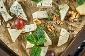 Antipasto - a cheese plate. Different, homemade cheeses on a ceramic plate - brie, camembert, Dutch with honey and nuts. Wine appetizer. Top view food