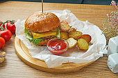 Juicy burger with beef, melted cheese, cucumber and young potato garnish on parchment. American fast food