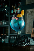 The bartender prepares an alcoholic cocktail. Decorating the drink with fruits and flowers. Blue cocktail in the beautiful glass at a bar the stands