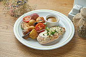 Baked chicken breast with cheese garnished with young potatoes and other vegetables in a white plate. Healthy, dietary food