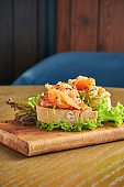 Appetizing bruschetta with salmon and lettuce on a cutting board on a wooden background. Close up, selective focus