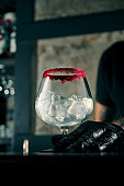 The bartender prepares an alcoholic cocktail. The process of creating a drink in a beautiful glass with ice
