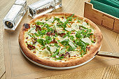 Appetizing baked pizza with wild mushrooms, parmesan and arugula with crispy crust on a wooden background. Restaurant table setting. Close up