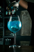 The bartender prepares an alcoholic cocktail. The process of pouring blue liquid from a shaker into a beautiful glass with ice at the bar. Bar accessories
