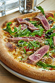Appetizing baked pizza with tuna, arugula, cherry tomatoes and parmesan with crisp on a wooden background. Restaurant serving. Seafood pizza