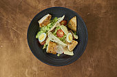 Caesar salad with croutons, parmesan, bacon, chicken, egg in black bowl on copper background. Restaurant serving. Close up with copy space.