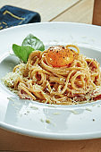 An appetizing portion of homemade Italian carbonara pasta(spaghetti) with egg yolk, bacon and parmesan in a white plate on a wooden background. Restaurant table setting