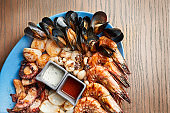A large plate of fried seafood - squid, octopus, mussels, scallops, shrimp. Assorted seafood on a ceramic plate on a wooden background. Film effect during post. Soft focus