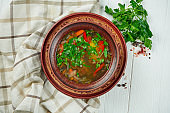 Close up view Chorba soup or stew with beef, herbs and hot pepper in brown bowl on wooden background, Traditional Turkish cuisine