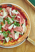 Appetizing baked pizza with prosciutto di parma, parmesan and arugula with crispy crust on a wooden background. Restaurant table setting. Top view