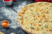 Baked pizza with 4 types of cheese, white sauce and on a black wooden background in a composition with ingredients. Top view