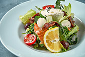 Appetizing salad with tomatoes, salmon, anchovies and cream cheese in a white plate. Concrete background
