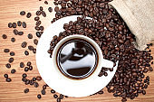 Coffee beans with black coffee on a brown wood background, top view.