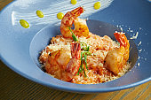Risotto of rice with shrimps. Rice with seafood in a blue bowl against a wooden background. Italian cuisine