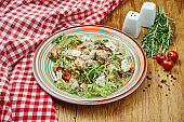 Delicious salad with seafood - salmon, shrimps, squid, lettuce and feta cheese in a ceramic plate on wooden background. CLose up