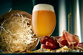 Cool craft wheat beer in a classic glass with snacks on the background of metal containers.