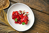 Airy cakes with white cream, strawberries, jam in a white bowl on a wooden background. Dessert Anna Pavlova