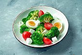 Fresh and healthy salad with broccoli, egg, feta cheese and tomatoes in a white bowl on a gray background