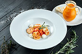 Appetizing, Spanish tomato soup with shrimp and mozzarella in a white plate on a black wooden background. Restaurant serving. Close up