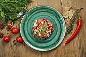 Salad with tomatoes, canned mushrooms, onions and boiled beef on a blue plate on a wooden background. Slavic salad medina. Close up