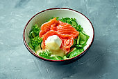 Appetizing salad with salmon, poached egg, hollandaise sauce and lettuce in a white bowl on a gray background