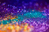Festive twinkle glitters background, abstract sparkle backdrop with circles,modern design overlay with sparkling glimmers. Yellow, blue, purple and green backdrop glittering sparks with glow effect.