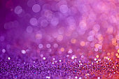 Decoration twinkle lights background, abstract sparkle backdrop with circles,modern design overlay with sparkling glimmers. Purple, pink and golden backdrop glittering sparks with blur effect.