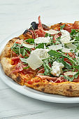 Appetizing homemade pizza with jamon, parmesan, arugula and straccella cheese on a white plate on a white wooden background