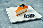 Appetizing dessert - cheesecake with caramel and berries in a white plate. Tasty pastry