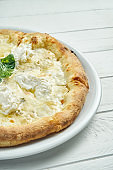 Appetizing, homemade 4 cheese pizza with blue cheese, mozzarella, parmesan and strachatella on a white plate on a white wooden background