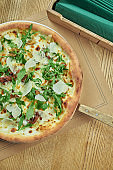 Appetizing baked pizza with wild mushrooms, parmesan and arugula with crispy crust on a wooden background. Restaurant table setting. Top view