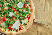 Appetizing baked pizza with salmon, cherry tomatoes, parmesan and arugula with crispy crust on a wooden background. Restaurant table setting. Selective focus, close up