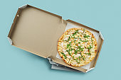 Conceptual poster for food and pizza delivery. Meat pizza in a cardboard box for delivery on a blue background with place for text