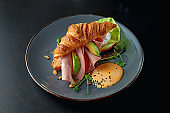 Perfect breakfast - croissant sandwich with mortadella sausage, avocado and cheese sauce in a gray plate. Selective focus