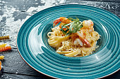 Appetizing homemade pasta with shrimp and creamy sauce in a blue plate. Close up, top view. Italian spaghetti, photo for the recipe