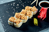 Appetizing Japanese sushi rolls - spicy with eel on a black board on a gray background