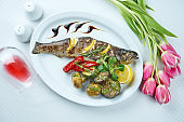 Delicious grilled seabass with lemon and a side dish of grilled vegetables (mushrooms, tomatoes, bell peppers) on a white plate. Top view, restaurant serving