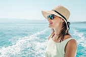 Smiling young woman wearing sunglasses, yellow dress and straw hat standing on a boat during summer vacation enjoying the fresh sea air and ocean view