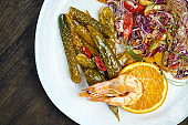 Asian salad with pickles, peppers, large shrimp and cabbage in a white plate