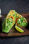 Vegetarian burrito with rice, tomatoes, corn and bell pepper in green pita on a brown plate with tomato salsa and guacamole. Vegetarian Shawarma Roll