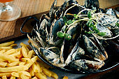 Tasty and fresh seafood - boiled mussels fried in creamy garlic sauce in a metal bowl. Beer snack. Selective focus. Tasty food