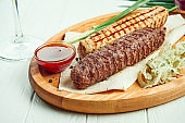Classical arabic beef or chicken Lula Kebab with onion garnish on wooden board. Appetizing meat on the grill. White background.