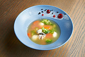 Appetizing and healthy seafood broth with broccoli, carrots, mozzarella and oysters in a blue, ceramic bowl on a wooden background. Film effect during post. Soft focus