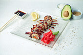 Sushi roll golden dragon with eel, unagi sauce on a white plate