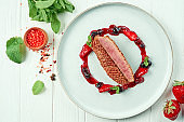 Appetizing roasted duck breast with berry jam in plate on a white wooden background in a composition with ingredients. Restaurant serving